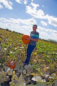 Michael McMillon, a freshman at Jamestown High School, inspects a ripened pumpkin.